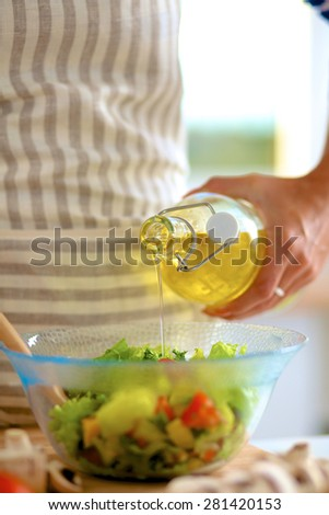 Young woman mixing fresh salad