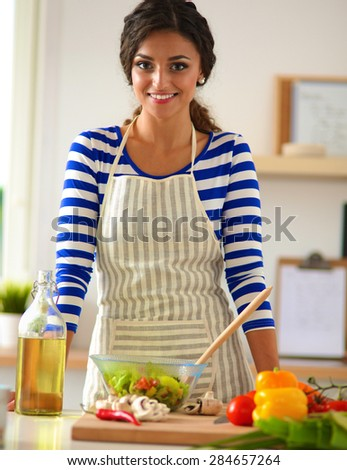 Young woman mixing fresh salad - stock photo