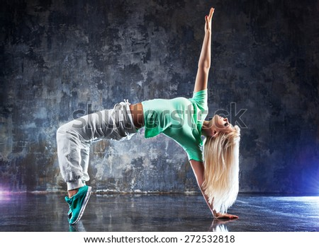 Young woman modern dancer. On dark stone wall background. - stock photo