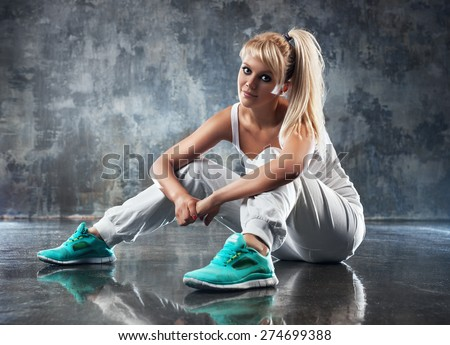 Young woman modern dancer sitting on floor and looking on camera. - stock photo