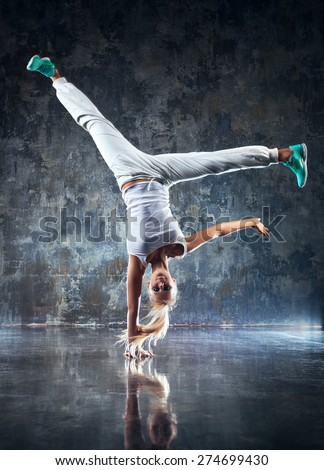 Young woman modern dancer standing on one hand. On stone wall background. - stock photo