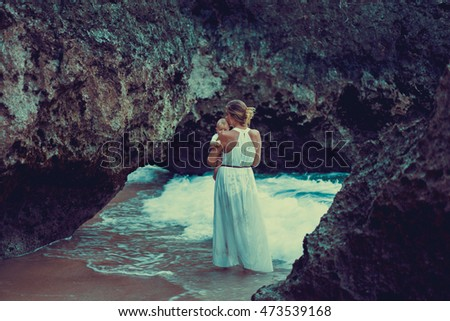 young woman mother holding a baby stands between rocks in the incoming wave. newborn baby in the arms of my mother on the ocean.