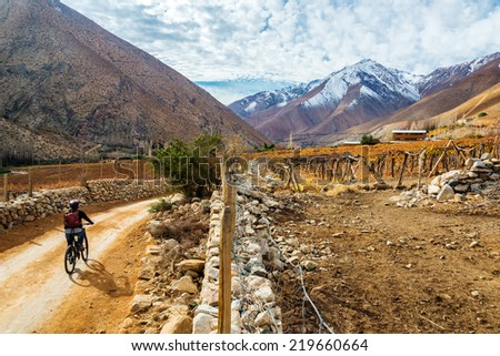 Young woman mountain biking in the Elqui Valley near Vicuna, Chile with the Andes mountains in the background - stock photo
