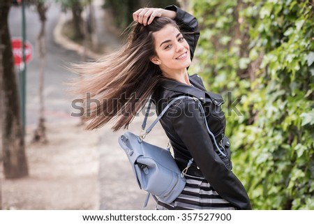 Young woman moving her hair in urban background wearing leather jacket - stock photo