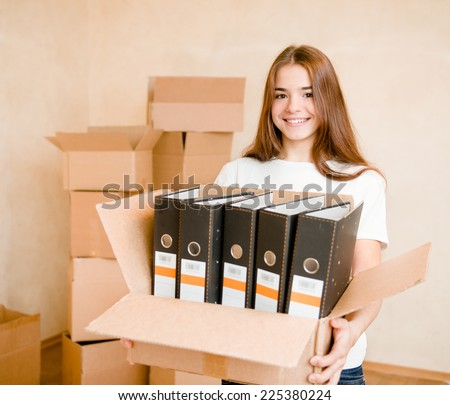 Young woman moving house to new home holding cardboard boxes - stock photo