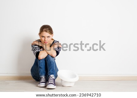 Young woman moving to new apartment and thinking of room furnish. Real estate credit and insurance concept. - stock photo