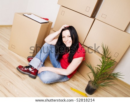 young woman moving to new house - stock photo
