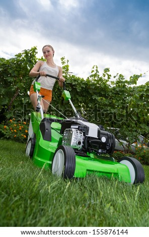 Young woman mowing the lawn - stock photo