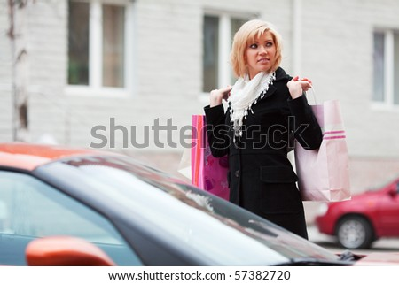 Young woman near a car after shopping. - stock photo