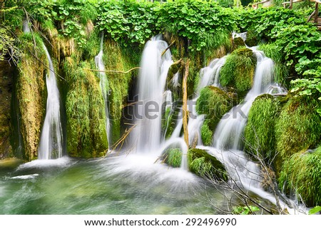 young woman near beautiful waterfalls on slopes of mountains - stock photo
