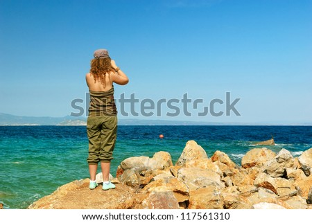 young woman near sea with binoculars