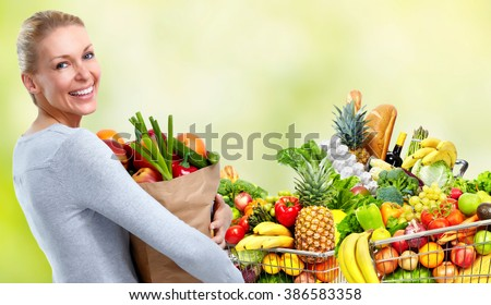 Young woman near shopping cart with food. - stock photo