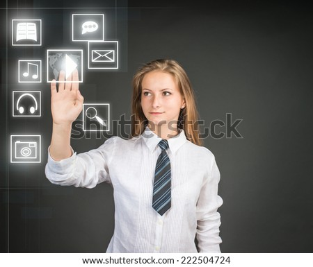 Young woman near visual screen virtual interface with web and social media icons. Teenager girl selecting pushing floating play icon. Technology concept. - stock photo