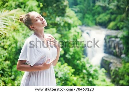 Young woman near waterfall, bali, indonesia - stock photo