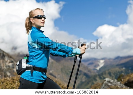 Young woman nordic walking and exercising in mountains, Nepal