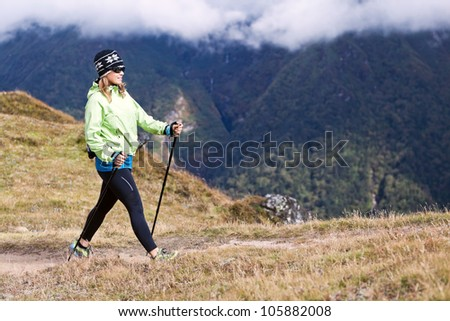 Young woman nordic walking in mountains, fitness and exercise outdoors. - stock photo