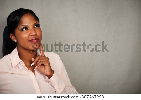 Young woman of african ethnicity looking away with a thinking gesture - copy space - stock photo