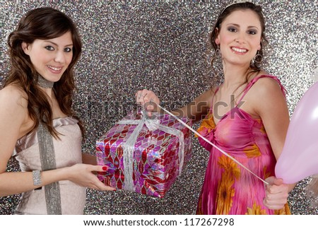 Young woman offering a gift to a birthday girl at a party. Girl opening a birthday present against a silver glitter background.