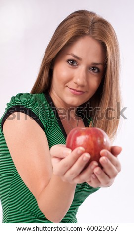 Young woman offering an apple selective focus - stock photo