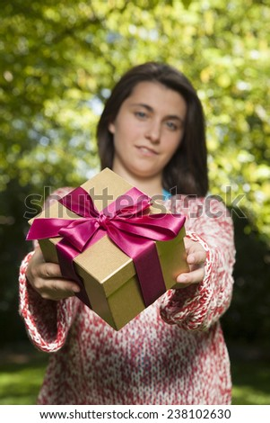 young woman offering golden red gift box over green tree background - stock photo