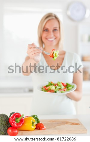 Young woman offering salad in the kitchen