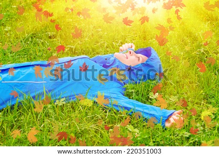 Young woman on a autumn day lying in grass