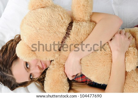 Young woman on a bed in an embrace with teddybear. Isolated on white background