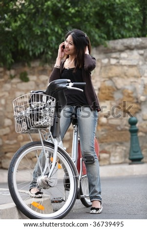 Young woman on a bicycle calling on her cell phone