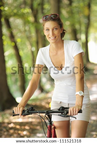 Young woman on a bicycle in the forest - stock photo