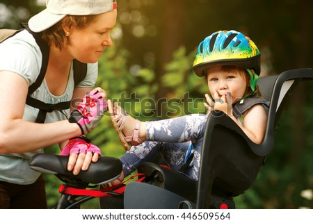 Young woman on a bicycle with little daughter - stock photo