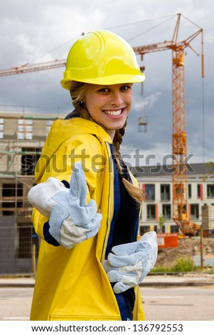 Young woman on a building site in workwear with thumb up