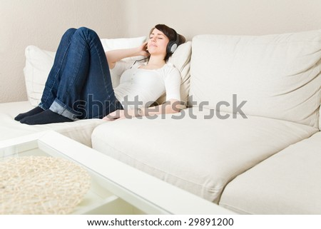 Young woman on a couch listening to music with headphones - stock photo