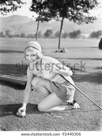 Young woman on a golf course placing a golf ball - stock photo