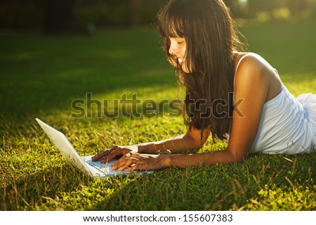 young woman on a grass in the park or garden using laptop
