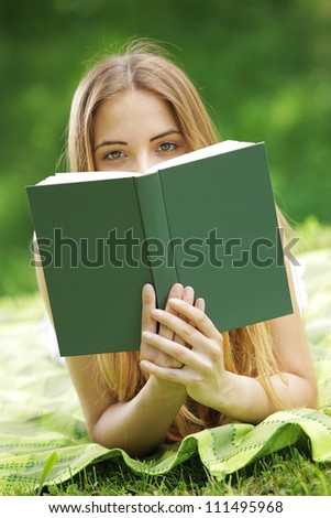Young woman on a grass looking over the book