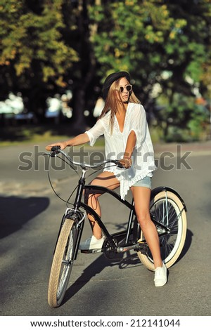 Young woman on a retro bicycle - stock photo