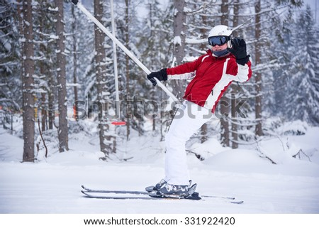 Young woman on a ski tow in red and white skiing suite waving with her hand - stock photo