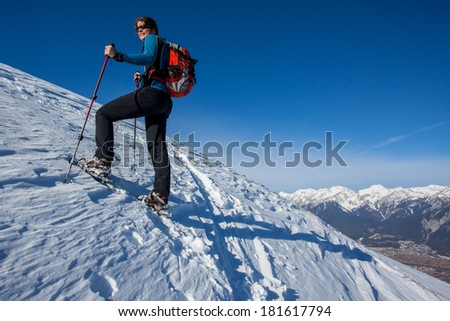 Young woman on a snowshoe trip in the moutains - stock photo
