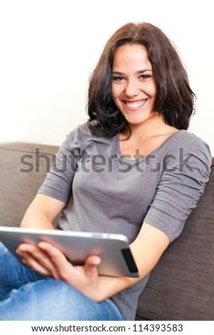 Young woman on a sofa surfing on a touchpad
