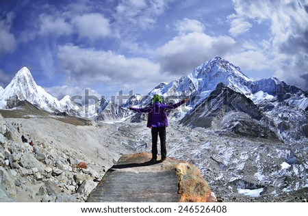 Young woman  on a stone   with raised hands,Nepal - stock photo