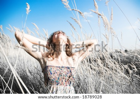 Young woman on a summer field. Infra-red photo effect.