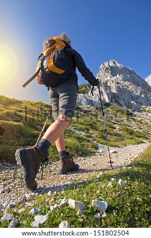 Young woman on a sunny day hiking in high mountains - stock photo
