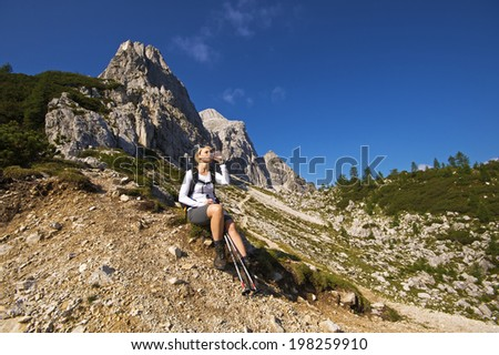 Young woman on a sunny day hiking in high mountains and drinking water - stock photo