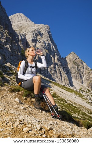 Young woman on a sunny day hiking in high mountains drinking water - stock photo