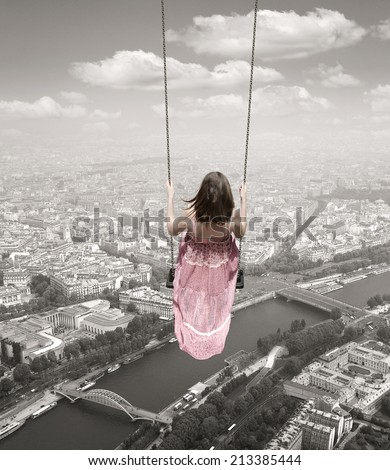 Young woman on a swing on the Paris town background. - stock photo