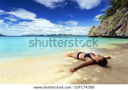 Young woman on a tropical beach. - stock photo