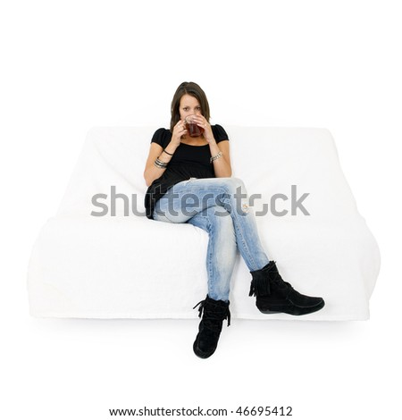 Young woman on a white couch drinking a cup of tea - stock photo