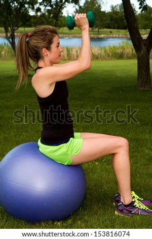 Young woman on an exercise ball, doing the seated dumbbell fly. - stock photo