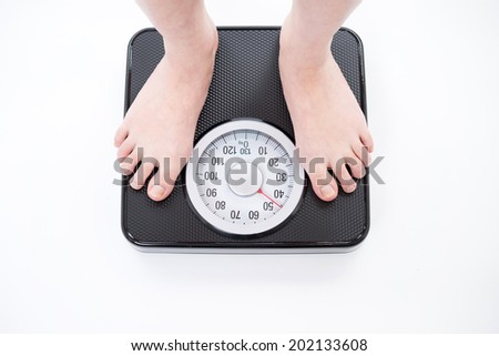 young woman on bathroom scale, isolated on white background - stock photo