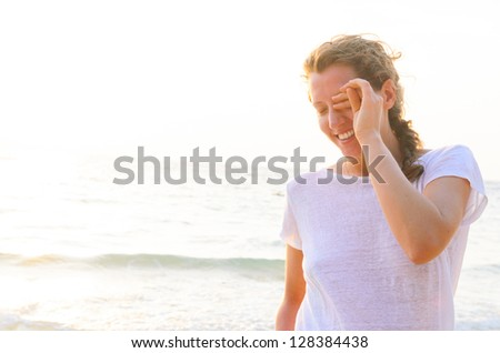young woman on beach at sunrise - stock photo